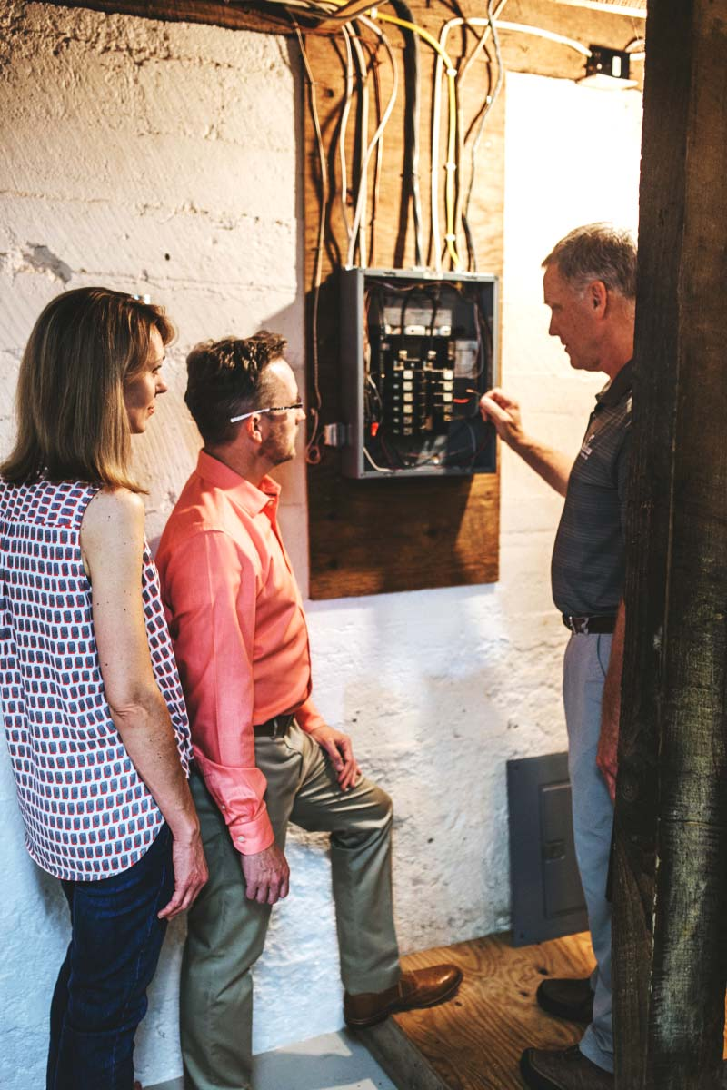 Rick Belliveau inspecting electric panel with couple